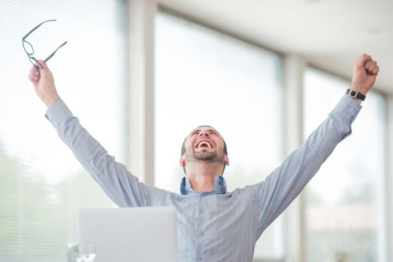 Picture of a man celebrating with his arms lifted in the air representing the happy clients that saved money by breaking their mortgage